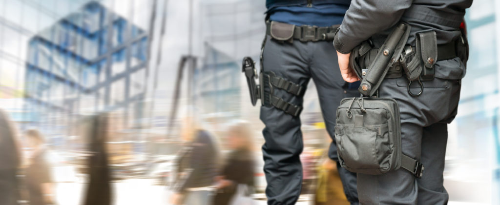 Armed policemen on guard in busy street with modern glass buildings and people walking